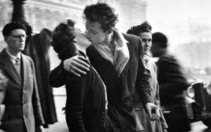 Due giovani che si baciano appassionatamenti fuori dall'hotel De Ville colti dall'obiettivo di Robert Doisneau