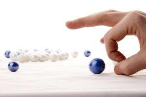 Una mano da una spintarella ad una pallina