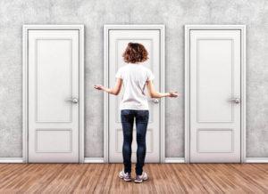 Una ragazza di spalle davanti a tre porte chiuse da scegliere