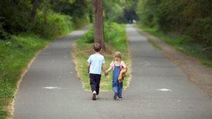 Due bambini si tengono per mano davanti ad un bivio