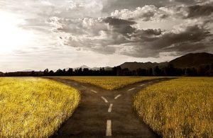 Una campagna con una strada asfaltata e un bivio con sullo sfondo le nuvole
