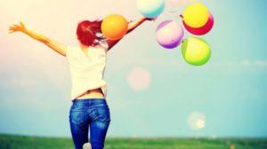 Una ragazza di spalle che esulta in un prato tra un volo di palloncini colorati