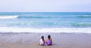 Due sorelline contemplano insieme il mare sedute a riva