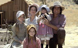 Papà, mamma, le tre figlie della famiglia Ingalls e sullo sfondo la loro casa nella prateria