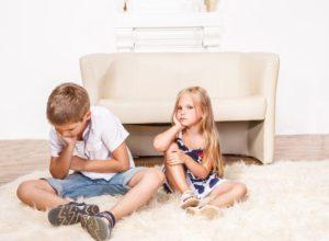 Fratello e sorella arrabbiati seduti sul tappeto del salotto