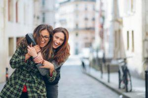 Due sorelle adulte e complici camminano per strada scherzando tra loro