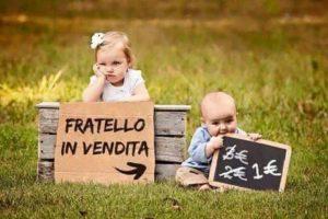 """Una bambina piccola sul prato col fratellino e un ironico cartello con la scritta """"fratello in vendita"""""""