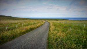 Una strada che attraversa una collina e sullo sfondo il mare