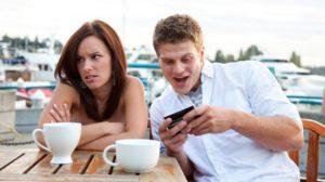 Un ragazzo che guarda lo smartphone con accanto una ragazza completamente disinteressata