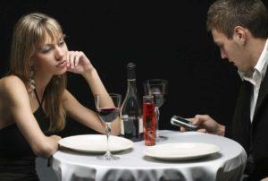 Una copia al tavolo del ristorante e lui che trascura lei guardando lo smartphone
