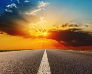 Strada asfaltata con linea di mezzeria e tramonto sullo sfondo