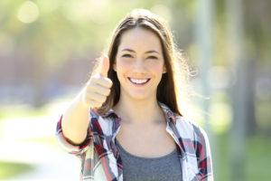 Una ragazza felice di essere una ragazza alfa e sorridente alza il pollice con assertività