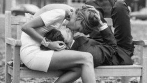Una ragazza alfa e il suo uomo si baciano con passione su una panchina del parco