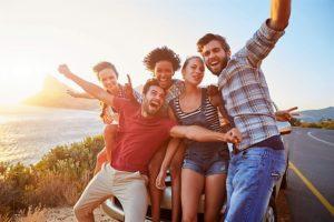 Un gruppo di giovani organizzata una gita al mare si fanno un selfie felici