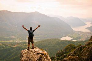 Un giovane uomo sopra una vetta ammira il panorama e alza le braccia in segno di vittoria per aver raggiunto l'obiettivo