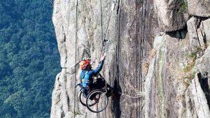 Un uomo che scala una parete di montagna verticale essendo in carrozzina perché disabile