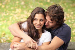 Un giovane uomo abbraccia la sua donna con energia e tenerezza seduti su un prato verde