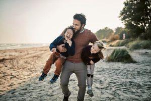 Un giovane papà porta sottobraccio con energia i suoi bambini divertiti in spiaggia