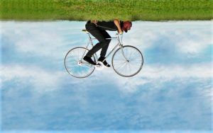Un uomo steso sul prato pedala la sua bicicletta per aria