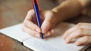 Una mano scrive su un quaderno con una penna blu ciò che ha fatto di buono per sapere chi è