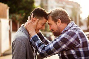 Un padre stringe tra le mani la testa e il viso del figlio giovane adulto per infondergli felicità e vitalità