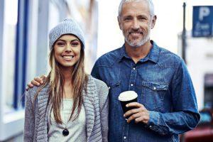 Un padre per strada sorridente con la sua figlia ormai grande le posa la mano sulla spalla come per sostenerla nelle scelte importanti