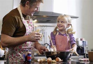 Un padre con la sua bambina cucinano sorridenti