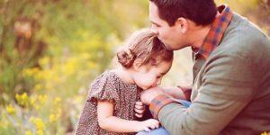 Un papà bacia sulla fronte la sua bambina mentre lei gli dà un bacio sulla mano e sullo sfondo un prato verde e fiorito