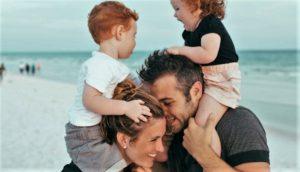 Mamma e papà portano sulle spalle sorridenti i loro figli piccoli abbracciandosi e sullo sfondo il mare