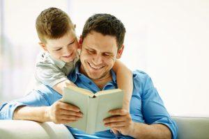 Un papà felice di leggere un libro al proprio bambino che lo ascolta interessato abbracciandolo