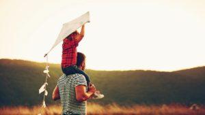 Un papà tiene sulle spalle il suo bambino che regge un aquilone e insieme guardano il cielo verso l'orizzonte