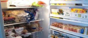 Un frigorifero aperto troppo pieno di alimenti per giunta spazzatura