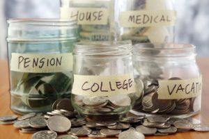 Cinque vasi di vetro contenenti i soldi destinati alle varie spese diverse