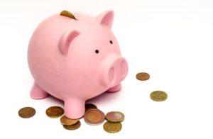 Il classico porcellino rosa-salvadanaio con alcune monete intorno