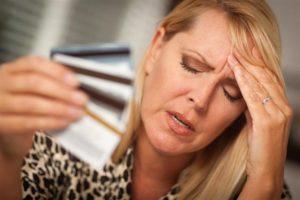 Una donna stressata occhi chiusi e mano sulla testa con un mazzo a ventaglio di carte di credito