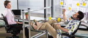 Un collega fannullone che ostenta serenità al lavoro con le gambe sulla scrivania