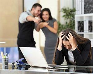 Una donna al computer con le mani tra i capelli e alle spalle due colleghi che si divertono