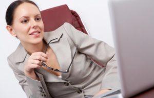 Una giovane donna al computer con gli occhiali in mano e un sorriso un po' sarcastico