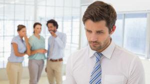 Un giovane uomo in ufficio colpito alle spalle dal sarcasmo e dalle frecciatine dei colleghi