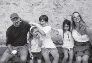 Steve Jobs con moglie e tre figli seduti su una panchina