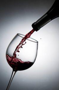Una bottiglia di vino rosso sta versando in un calice
