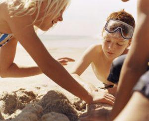 Una mamma costruisce castelli di sabbia in riva al mare col suo bambino