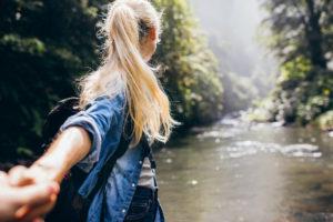 Una ragazza bionda di spalle si avventura nel bosco tenendo per mano qualcuno che vorrebbe trattenerla indietro