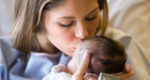 Una mamma bacia tenerissima la testa del suo bambino appena nato, ancora in sala parto