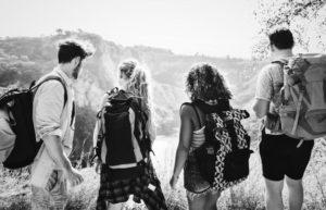 Quattro giovani adulti di spalle con lo zaino in un prato camminano insieme