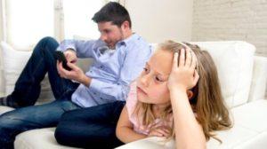 Un padre sul divano guarda lo smartphone e non la sua bambina
