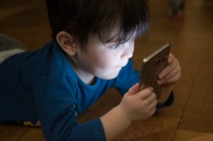 Un bambino che si morde le labbra troppo intento a guardare uno smartphone col viso illuminato dalla luce blu
