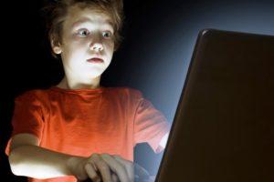 Un ragazzino spaventato davanti allo schermo di un pc