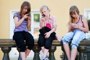 Tre ragazzine sedute su un muretto ognuna col suo smartphone non si guardano neppure