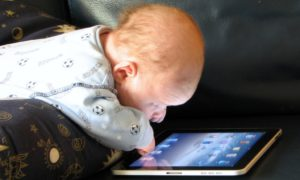 Un neonato riverso su un Ipad con gli occhi spalancati sulla luce blu del touchscreen